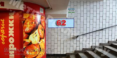 """Станция """"Новогиреево"""". Южный подземный вестибюль станции. Подуличный переход, выход пассажиров в город из стеклометаллических дверей налево. Информационный указатель размером 1,2 х 0,4 м. Рекламное место ?? 62"""